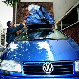 Mannen maken de auto gereed om naar Marokko te vertrekken.