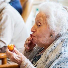 Een bewoonster van een verpleeghuis geniet van een oranjesoesje. Goede mondzorg draagt bij aan een betere kwaliteit van leven.