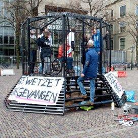 Gehandicapte jongeren en sympathisanten voeren actie in een kooi op het Plein in Den Haag tegen het wetsvoorstel werken naar vermogen.