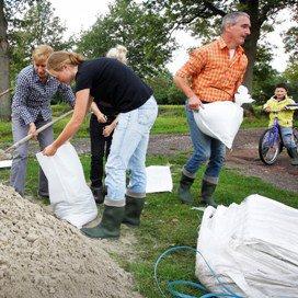 Buurtbewoners in De Lutte helpen elkaar met het vullen van zandzakken om het water van De Dinkel buiten de deur te houden.