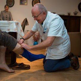 Verpleegkundige en zzp'er Jan helpt een cliënt met steunkousen.