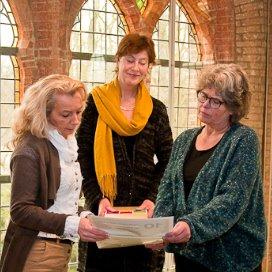 Marijke Vos (m) en Sociaal Werker van het jaar Antoinet Wijnakker (l) bieden Jantine Kriens (VNG) het campagnemateriaal aan.