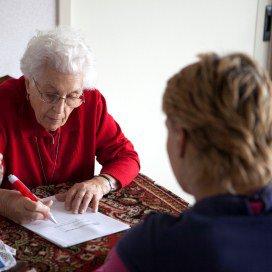 Wijkverpleegkundige met cliënt aan de keukentafel