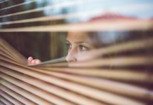 vrouw kijkt door luxaflex